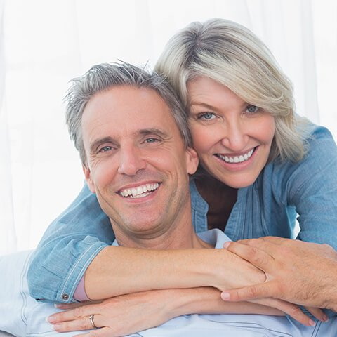 Couple hugging with healthy, functional smiles thanks to their dentist in Lititz, PA Dr. Berg