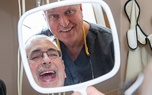 A patient smiling with Dr. Berg admiring the difference his smile makes